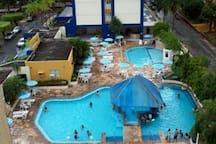 Área de lazer com 2 piscinas grandes, 1 menor com cascata, 1 jacuzzi coberta e 1 infantil