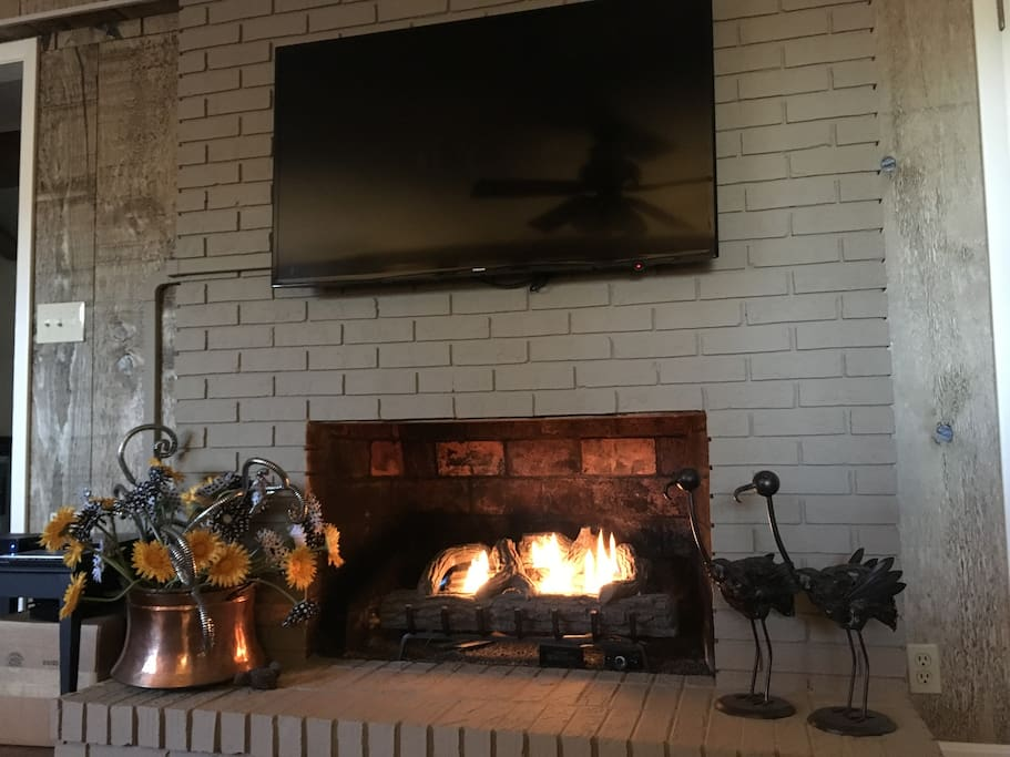 Fireplace with gas logs and 50-inch flat screen TV