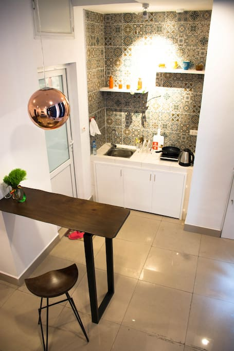 The kitchen furnished with fridge, induction cooker, tableware, electric kettle...