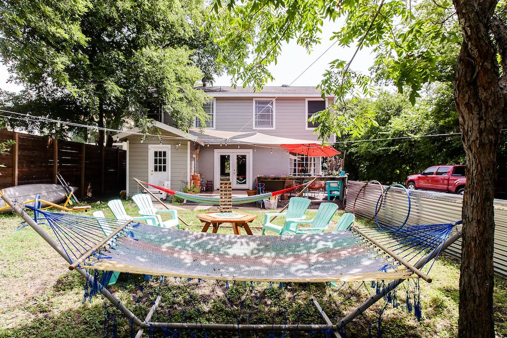 Backyard with seating for 15 plus two hammocks, darts, giant jenga, hula hoops, horseshoes, sandbox, trampoline, and back deck with additional seating for 15 with umbrella and table