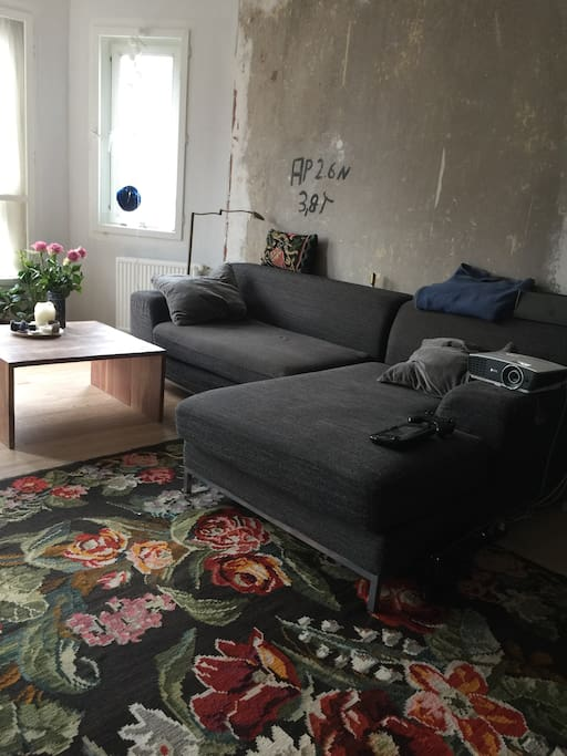 Bright living room with a cosy sofa and beamer.
