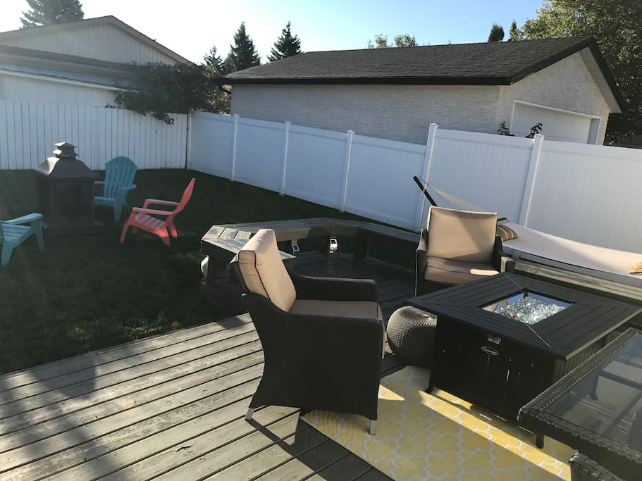 Back yard with fire pit, fire table and hammock. Tons of seating!