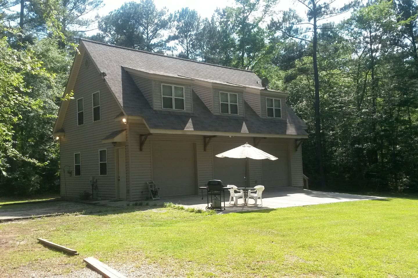 Front. Parking to left. Open slab patio area w/ picnic table & gas grill