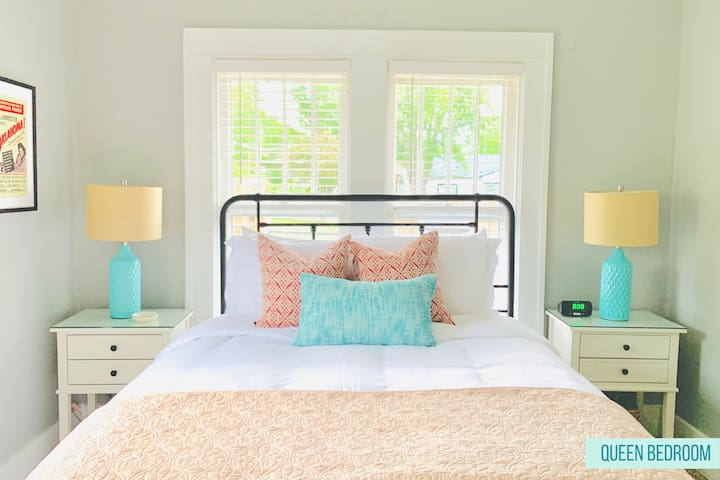 This queen bedroom has a comfy bed, luxurious sheets, a comforter with duvet and/or coverlet. The room also has a ceiling fan, desk fan, plenty of electrical outlets, extra blankets, a bedside USB charging station, desk, and several mirrors.
