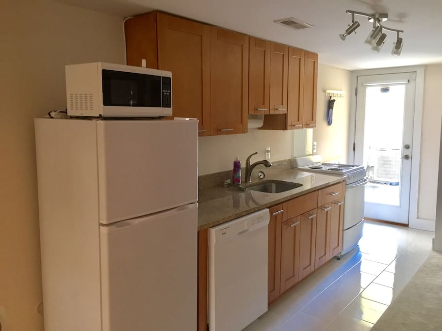 Kitchen includes stove, fridge, microwave, dishwasher, and cooking essentials.