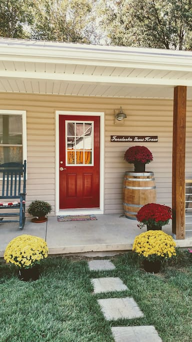 "The bright red door and seasonal decor will be ready to greet you with a big, ""Welcome!"""