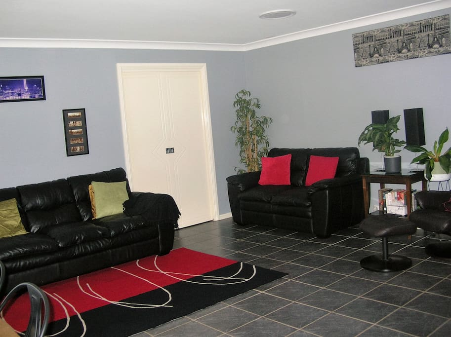 Comfortable leather lounges, smart TV and practical tile floor in the lounge room