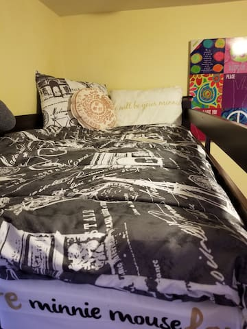 Twin bed of two beds room. Twin stacks on full bed for additional space in room.