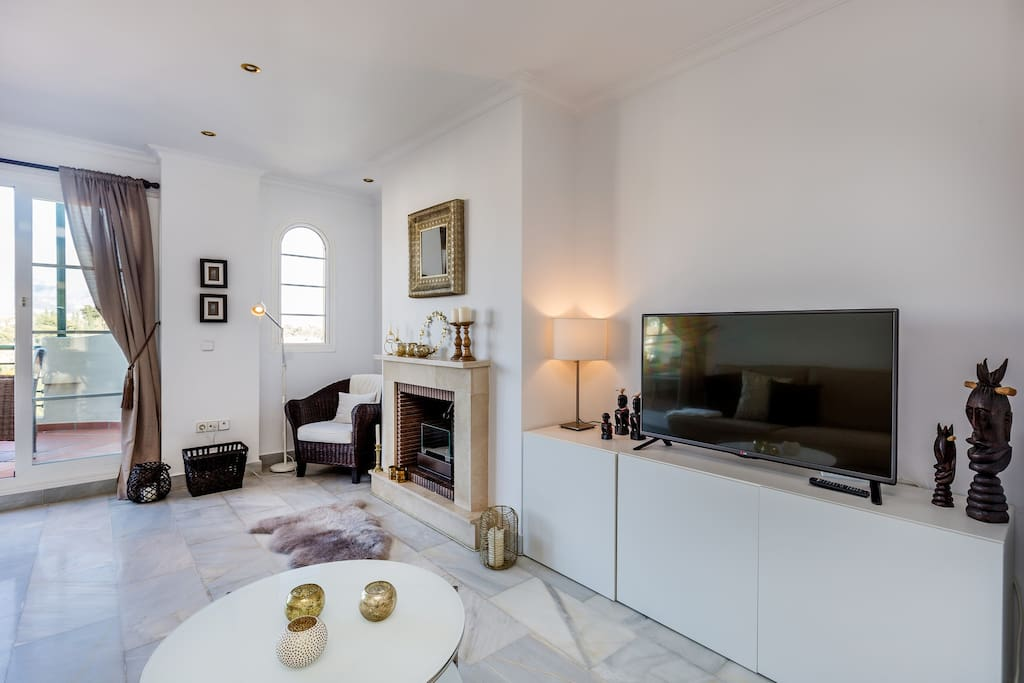Ample and well appointed living room with fireplace apartment with sea views for rent by Puerto banus with pool