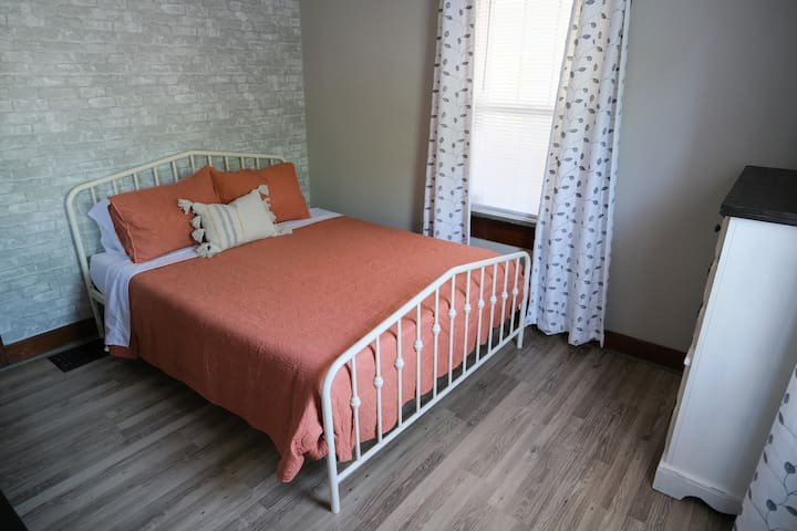 Bedroom 1 features two large dressers and this gorgeous bed frame, quilt, and plush blanket. The lamp has a USB port for charging your devices.