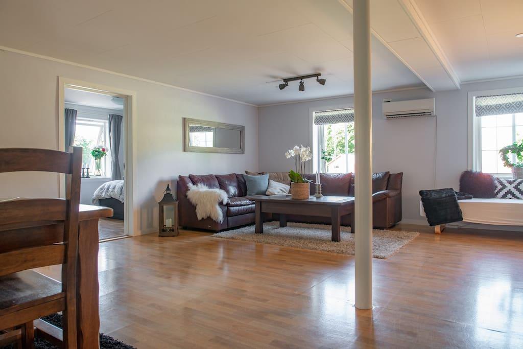 Lys og romslig stue med plass til både sittegruppe, spisestue og en sengeplass.