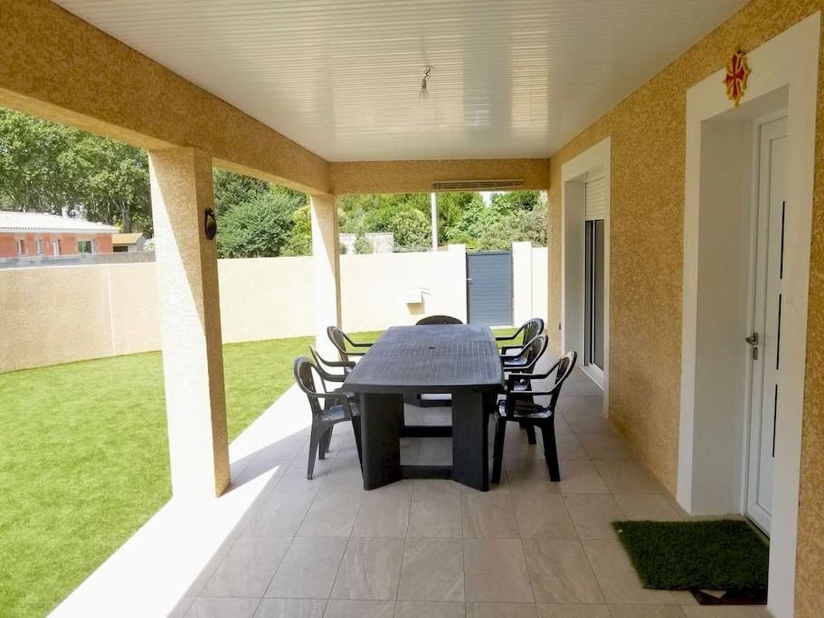 Grande terrasse couverte avec table. Covered porch with a  big family style table.