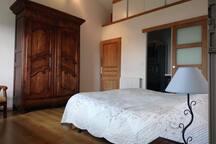 Chambre installée avec lit double, wc (porte de gauche), salle de bain avec douche.