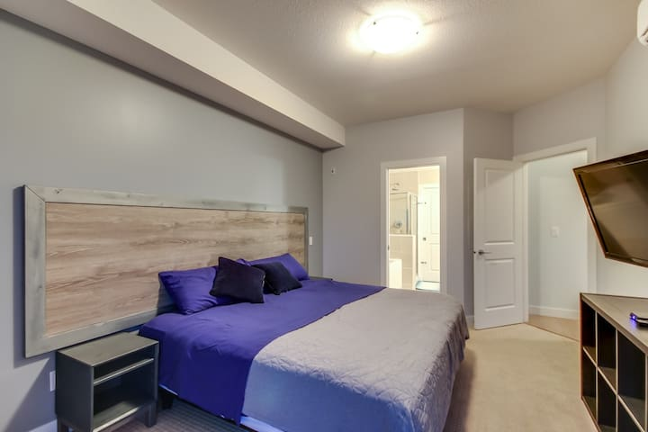Master Bedroom. King bed. In 2020 we added bedside lamps and artwork.   Bedroom also has a round nesting/reading chair in front of a second set of patio doors to the xl deck, and outdoor couch.