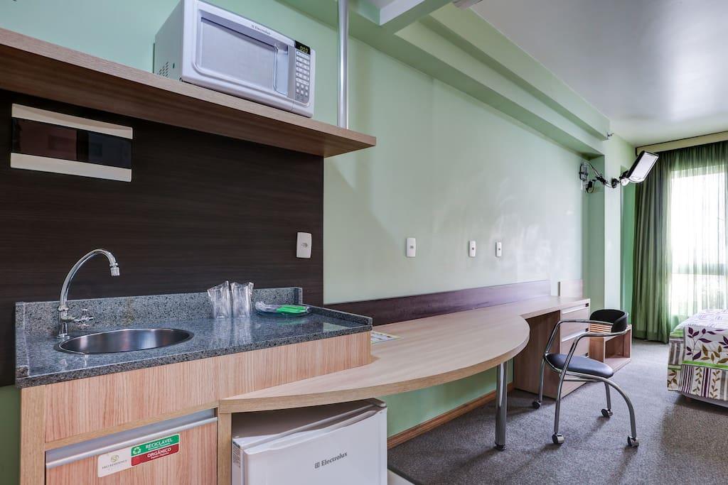 Cozinha compacta e mesa de trabalho.