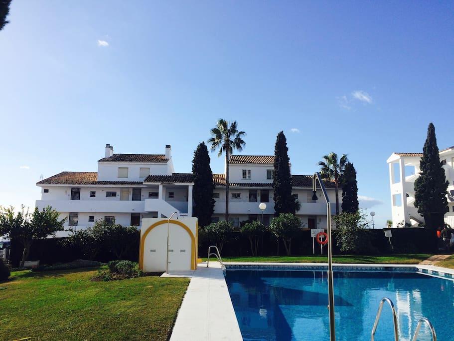 Edificio del apartamento y piscina de la urbanización.