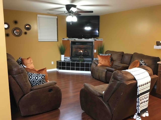 """Open living area concept with gas fire place 60"""" Flat screen for The Whole family to enjoy during a relaxing moment after a full day of adventure and fun!"""