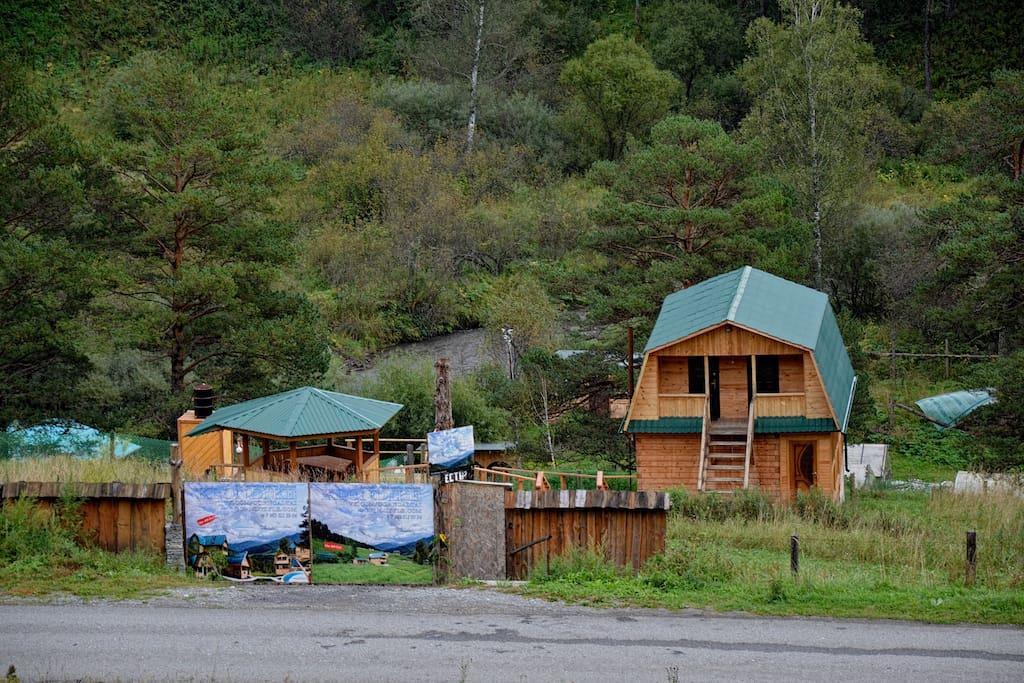 """Дом """"Комфорт""""  ------------------- Описание дома: У подножия горы стоит всесезонный двухэтажный дом для ценителей комфорта! Дом оснащен всеми необходимыми коммуникациями для цивилизованного проживания. На всех этажах есть балкон, с которого открываются красивые виды на местность, до начала летнего сезона можно понаблюдать за гуляющими маралами на противоположной горе. Дом состоит из двух номеров на 10 человек, в каждом номере предусмотрены дополнительные места. При доме находится: уличная беседка с бесплатным мангалом, к которому прилагается одна вязанка дров на номер. В 10 метрах находится баня, летний душ. В холодное время дом отапливается."""