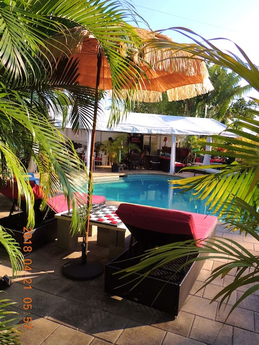View from lounge chairs to outside living room, dining room, kitchen and bar set under 1000 sq ft gazebo
