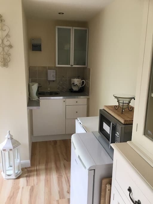 Kitchen area with microwave and fridge, cooker oven and kettle and toaster. All kitchen utensils supplied including cups, plates, pots, pans, cutlery etc