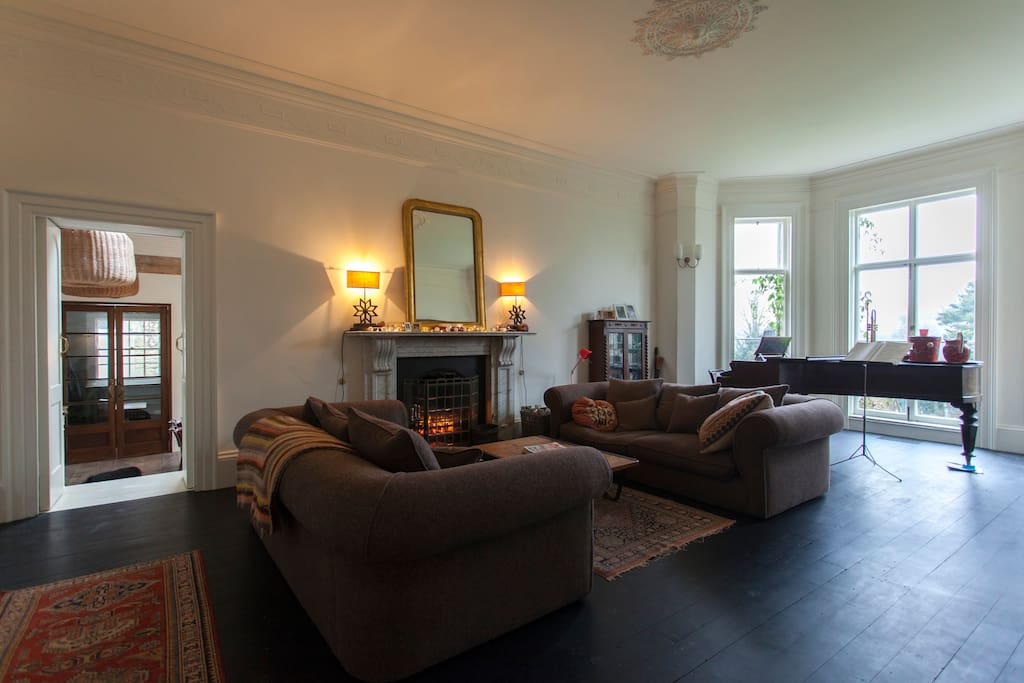 The Drawing Room with large log fire and grand piano