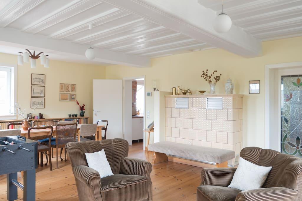 Großes Wohnzimmer mit Holzbohlendecke, Kachelofen - Blick Richtung Küche