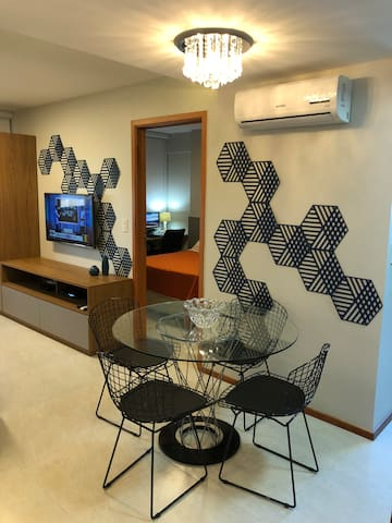 Sala com Smart TV UHD 4k, Ar condicionado e Mesa.