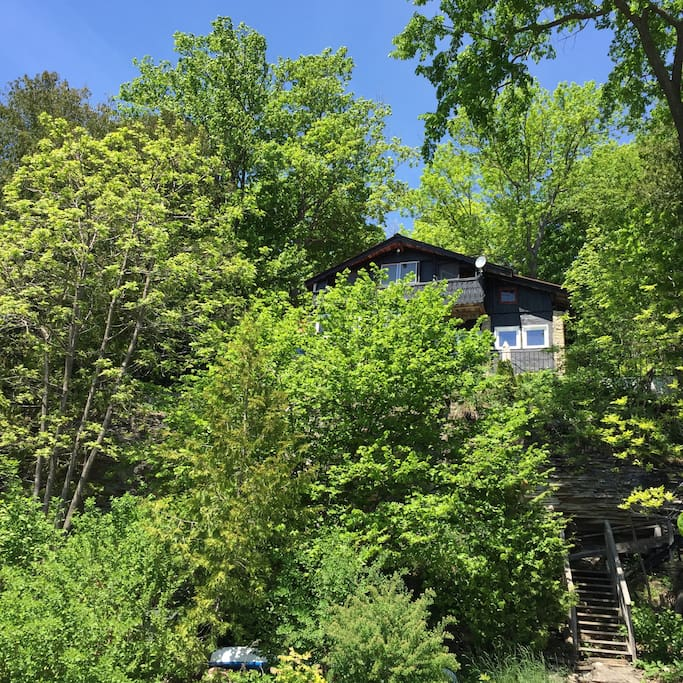 The cabin is hidden behind the trees in the summer and 75ft private water frontage is down about 30 stairs. The water has a rock bed (so bring water shoes). A fire and starry nights (perfect)!