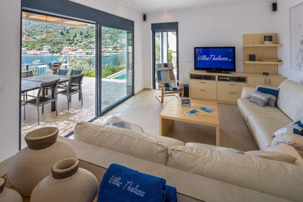 Living room with large openings on the terraces and Sivota's harbour
