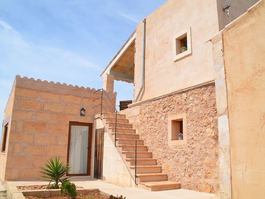 Vista lateral de la casa y del acceso a la habitación superior