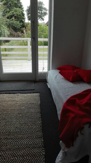 soveværelse med 1 gæsteseng med udgang til terrasse og have