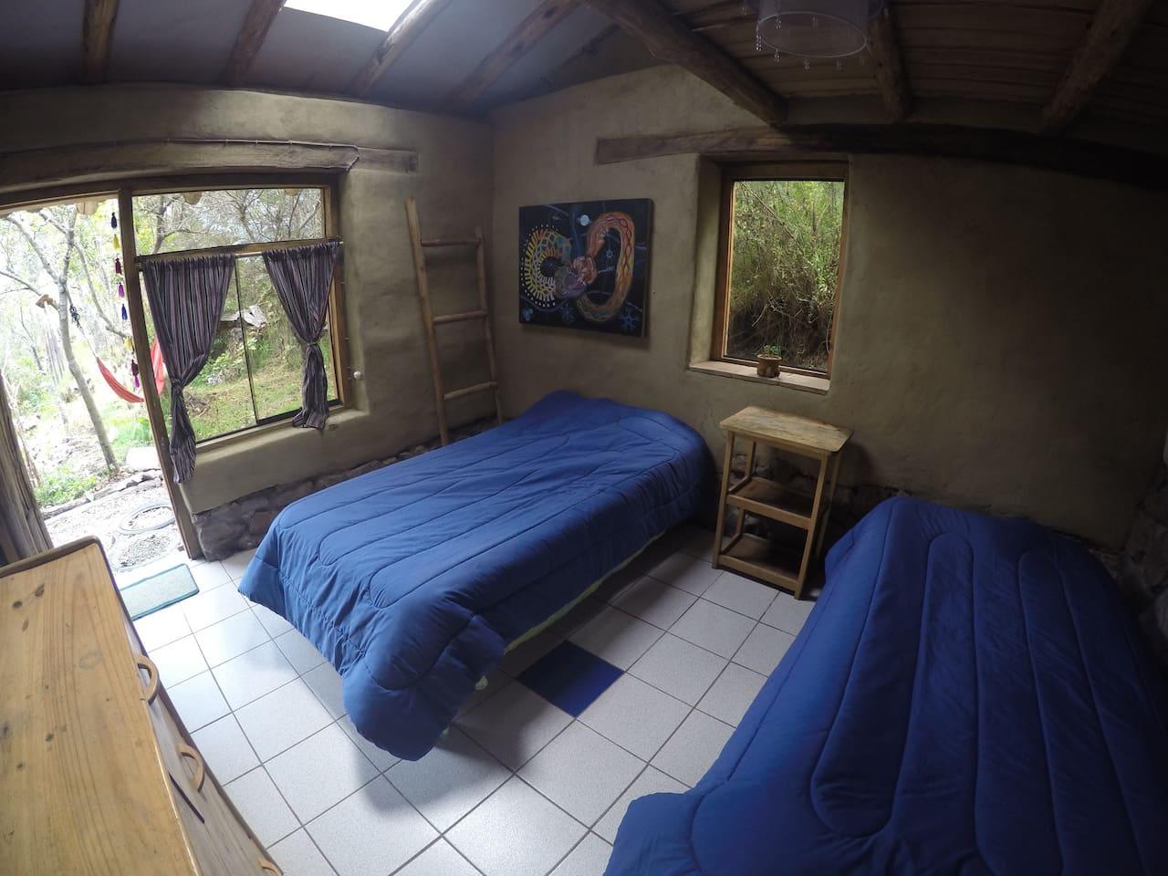 Habitacion con 3 camas, una de ellas en altilloy realizadas en bioconstruccion con materiales naturales de la zona.