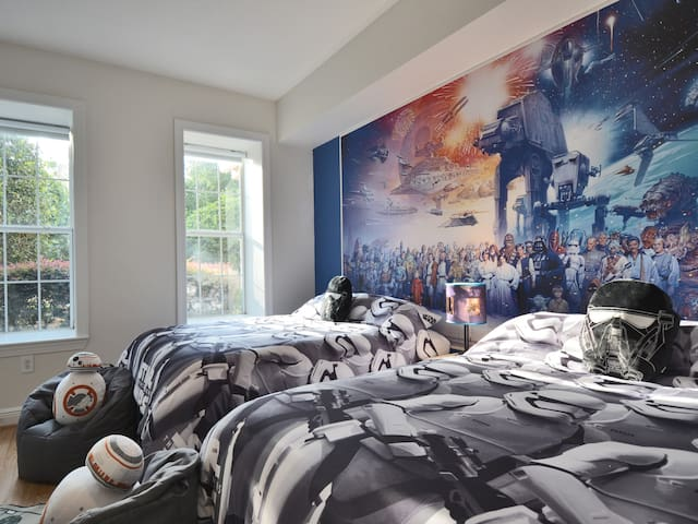 The Star Wars themed kids bedroom has 2 full size beds, a packnplay & high-chair