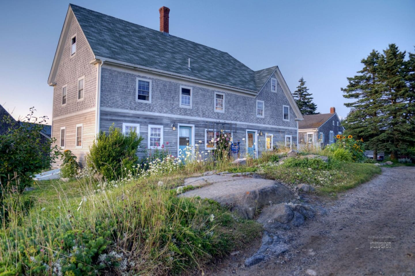 The John Sterling Harbor House sits on the side of the road. It is the first communal house on Monhegan and has been a landmark for over 200 years.