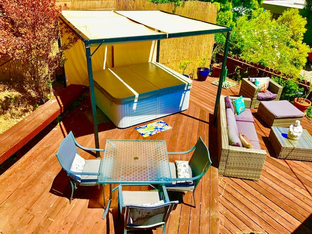 2-level outdoor deck with hot tub, outdoor living and dining furniture and hot tub. All with bay views! Surrounded by trees!