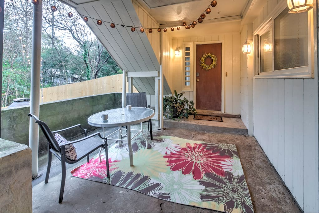 Private entrance into the apartment with outdoor seating space under warm string lights
