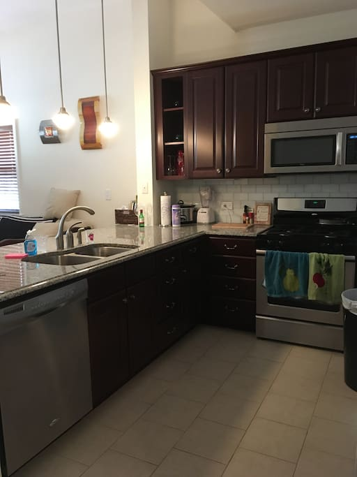 Modern apartment kitchen with high end stainless steal appliances and granite countertops.
