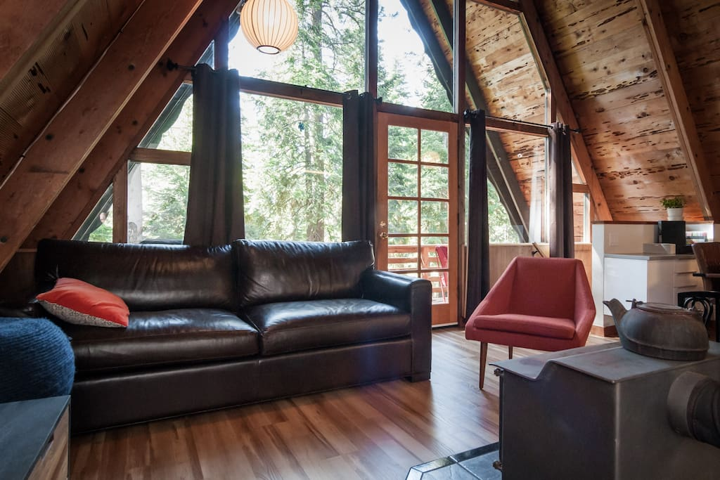 Cozy family room with comfortable leather couch, wood burning stove, tv, and open to dining area and kitchen.