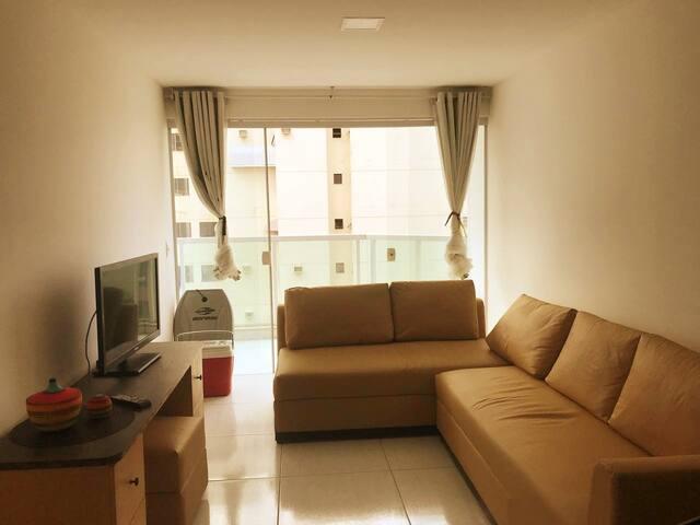 Sala de estar ampla pra descansar depois de um dia de praia! Detalhe para o cooler e a prancha disponível pra vc!