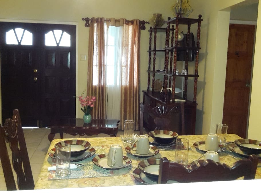 This photograph shows the dining and living spaces. In the background there is a door which leads to one of the private verandahs for this listings.