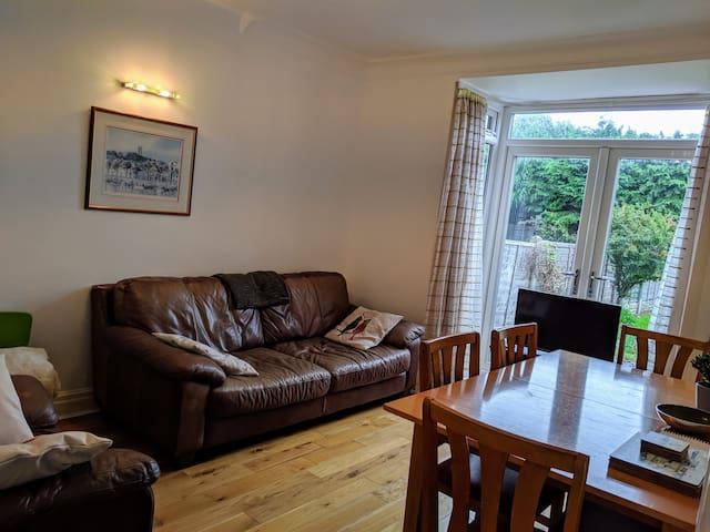 Living/ Dining Room. Extending Dining Table (Additional Chairs Under Stairs Cupboard), Amazon Fire TV, Large Leather Sofa and Armchair, Solid Oak Flooring, Leather Pouffe with Toys, Artwork, GCH Radiator