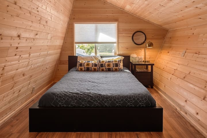 """Annex upstairs master bedroom with queen bed and 42"""" flatscreen TV."""