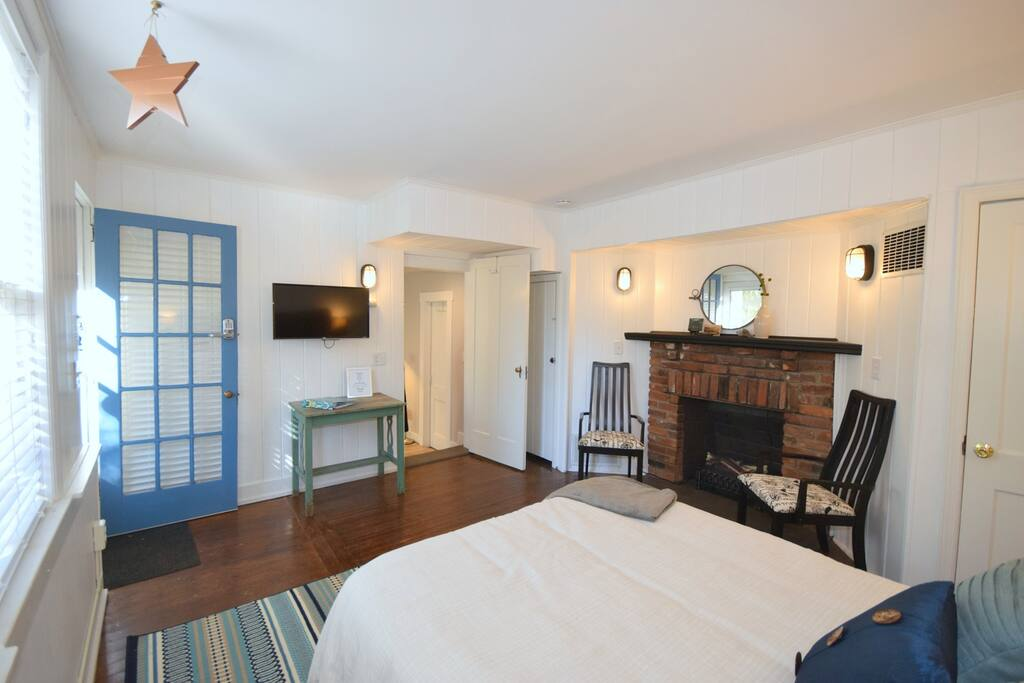 X-L bedroom, this view shows entry door, TV, fireplace with electric logs + heater, Queen size bed.