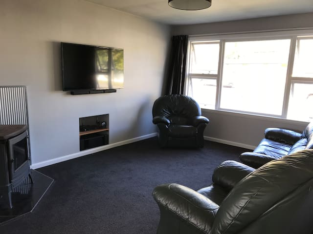 Living area with leather lounge suite smart tv and diesel fire for heating if required