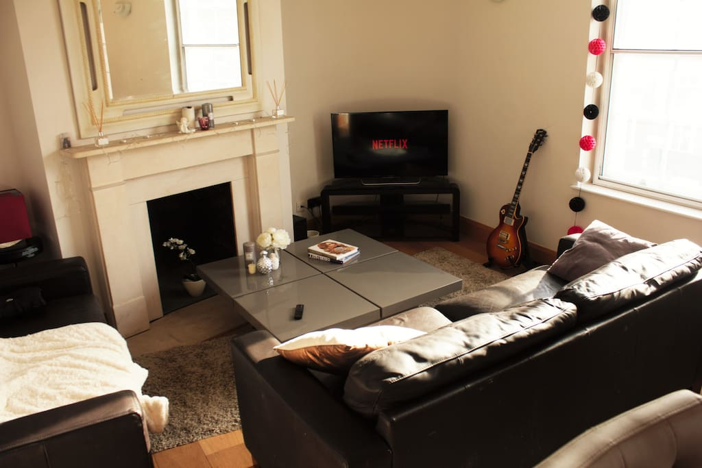 Cozy linving room, with 2 guitars and a fully connected smart tv