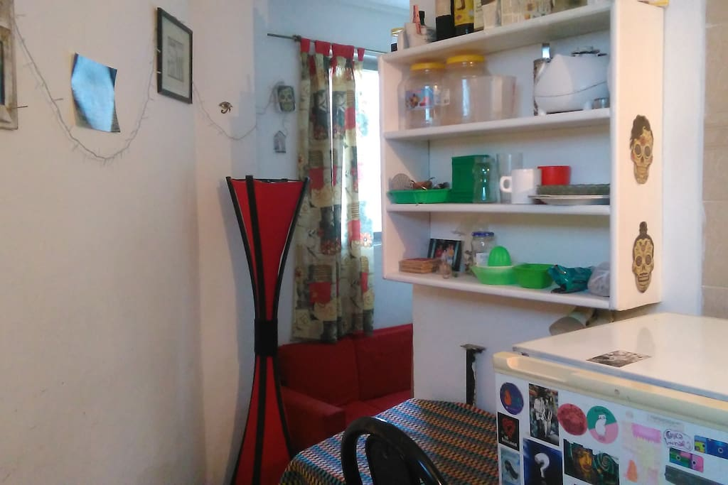 Living desde cocina Mesa fija en la pared y sillas. Elementos de cocina.