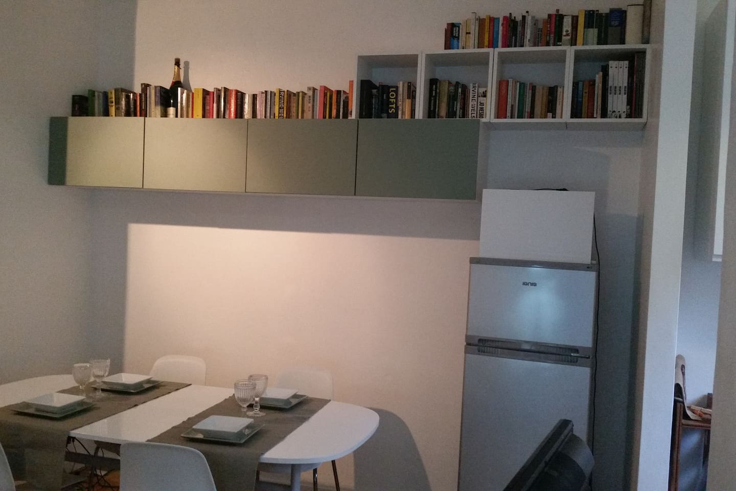 Dining table seating 4, wall cabinets holding assortment of glassware, crockery, plates, tablecloths and all that you need. Ample library with books in Italian & English. Microwave above fridge.