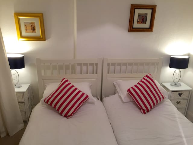 Upstairs twin room with view to village green. Side tables and table lamps.