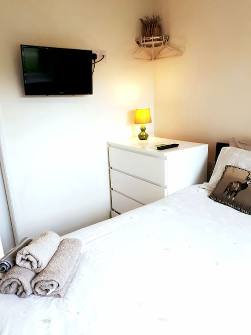 King sized bed with chest of drawers and wall mounted tv