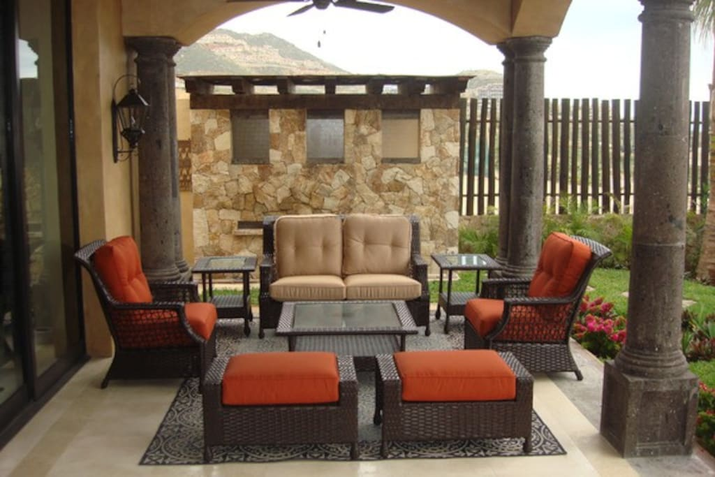 Back patio seating area; outdoor shower & bathroom in background